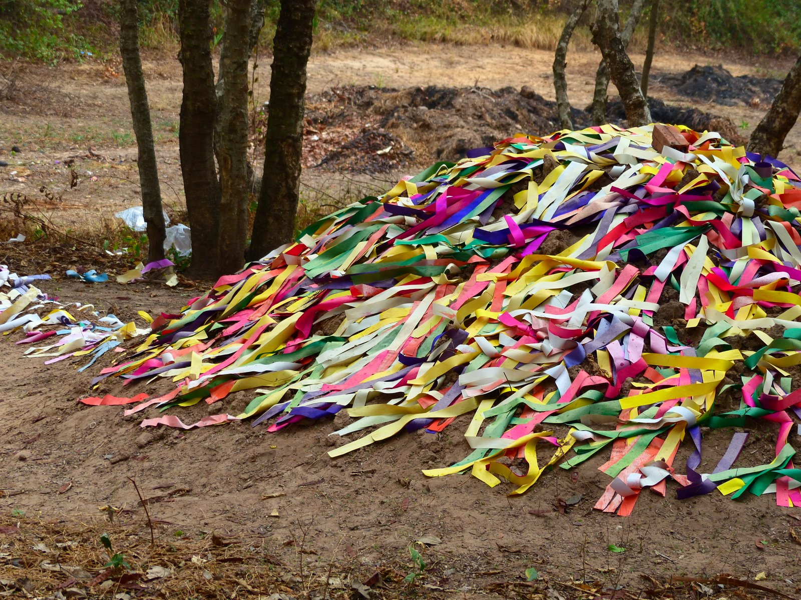 An unexcavated mass grave covered in brightly colored ribbons as tribute to the dead.