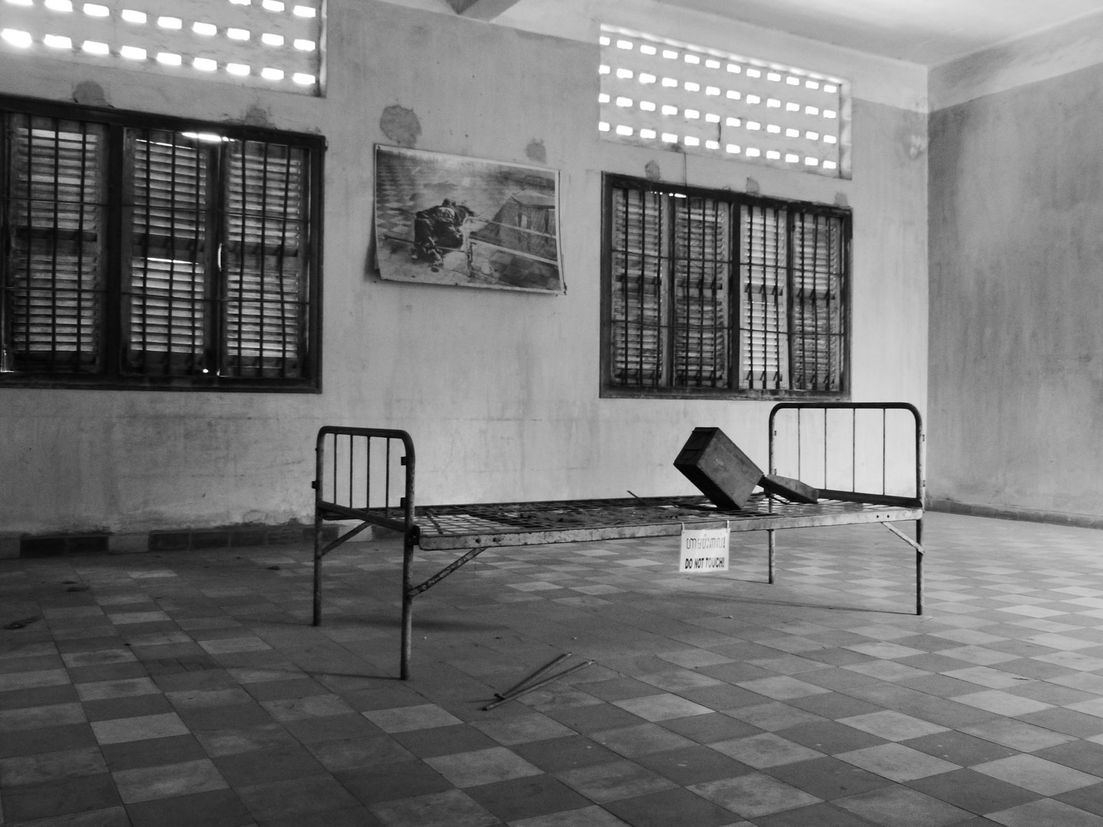 The Khmer Rouge kept detailed records and photographs. Hanging on the wall of this old classroom is a graphic photograph of a prisoner who was tortured in this very room on this very bed, most likely until he either confessed or died.