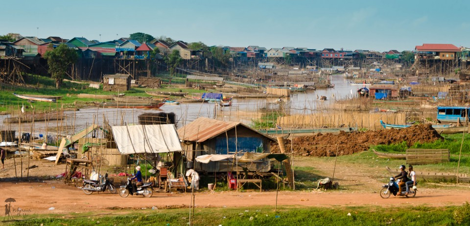 One of the local floating villages, Kamphong Kleang. It's the dry season, so it's not exactly floating right now. But once the rains come, the water will rise to be as high as the houses on stilts and that road and buildings in the lower part of the photo will be underwater.