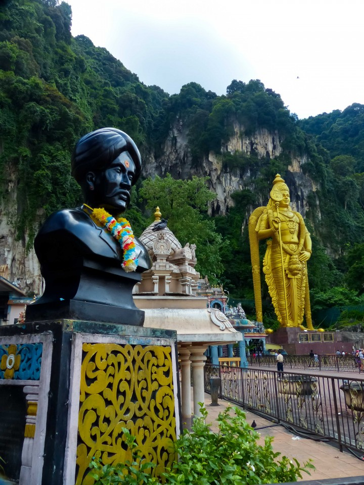 I believe this is a bust of ...with the large statue of Murugan in the background.