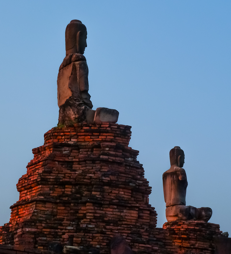 Sun sets over several Buddhas at one of the many ruined temples along the Chao Phraya river.