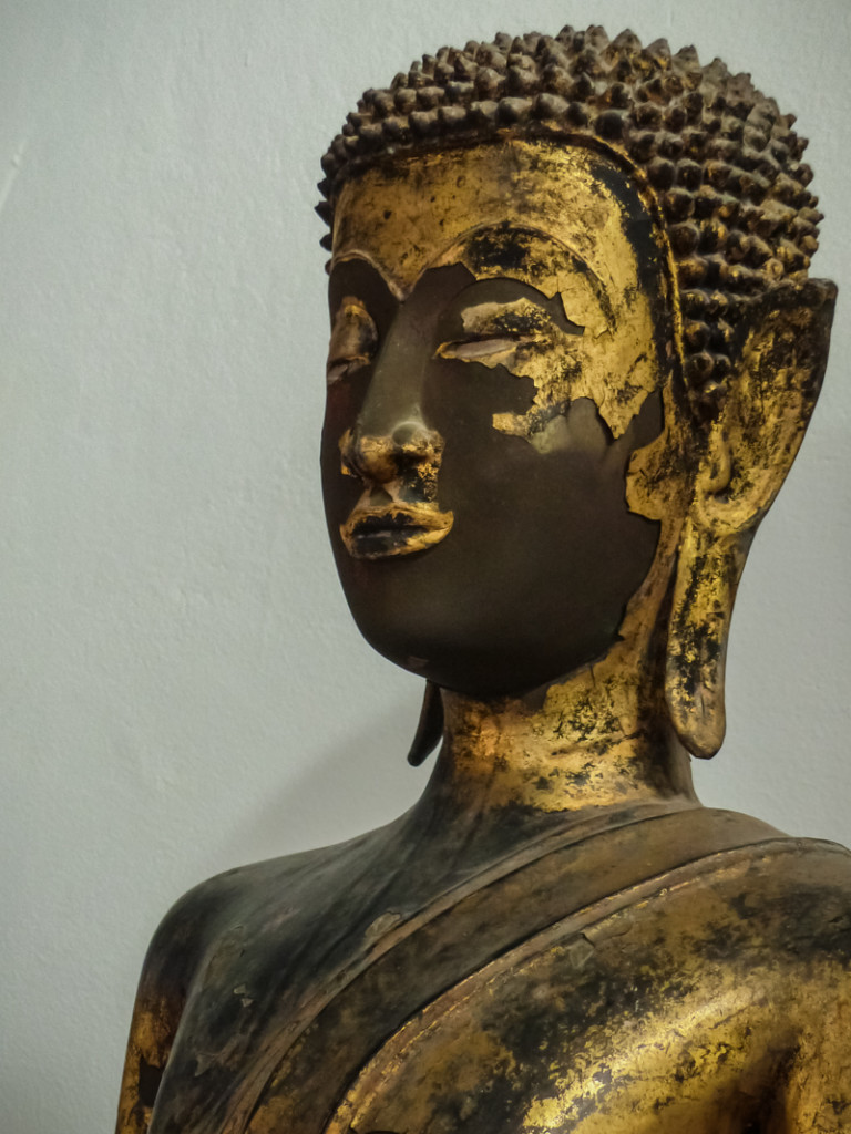 Gold leaf is flaking off this ancient golden Buddha.