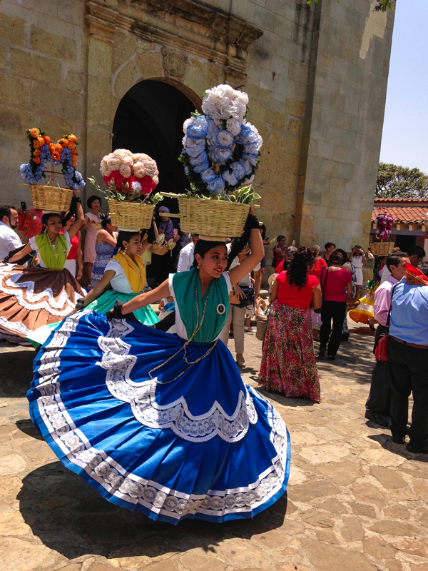 {China Oaxaqueña dancers at the celebration for a first communion in the churchyard of Santo Tomas - the oldest church in Oaxaca}