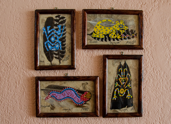 {We've finally started hanging art in our house - after delaying for a while so we could paint. But now it is too hot to paint until later in the year. So the art is now going up on the caucasian toned walls. These are by a local artist, Gagachitl, who paints these brightly colored images on feathers.}