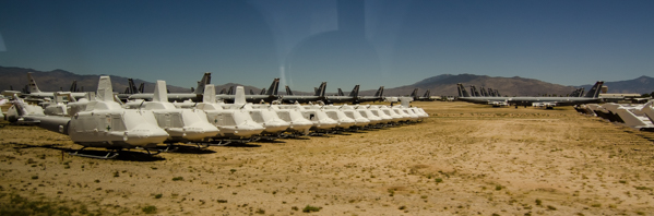 {Tucson is home to the Boneyard, the storage and salvage facility for all government aircraft. We took a tour out to see some of it. This is a row of helicopters, wrapped up in silicone to protect them. The climate in Tucson is perfect for preserving aircraft, dry dry dry}