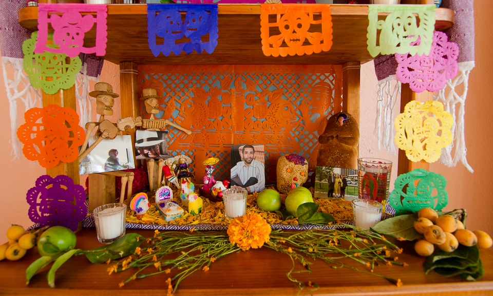 {Bottom level - flowers, fruits, papel picado, more photos of loved ones, pan de muerto, a skull made from amaranth seeds, more candles, & water}