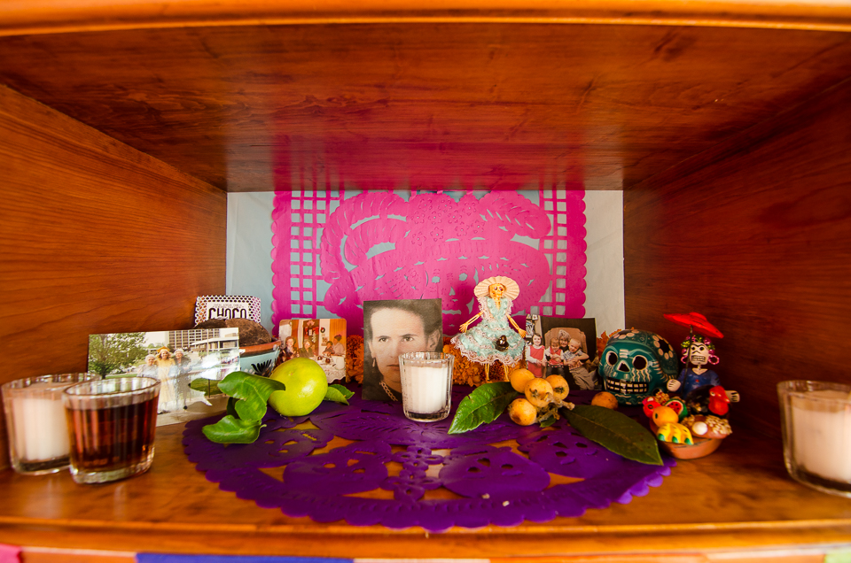 {Middle level - candles, mezcal, fruits, photos of loved ones, and funny little figures and scenes that we picked up in the markets}