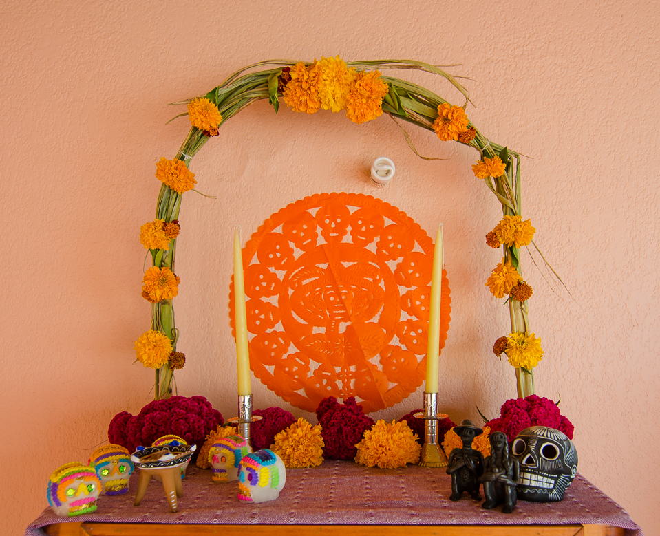 {Top level - arch with marigolds, sugar skulls, copal incense, and some pottery from the valley}