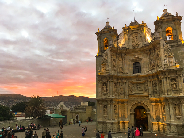 {The sun sets over La Basílica de la Soledad here in Oaxaca, as a young girl waits for her Quinceañera ceremony to start.}